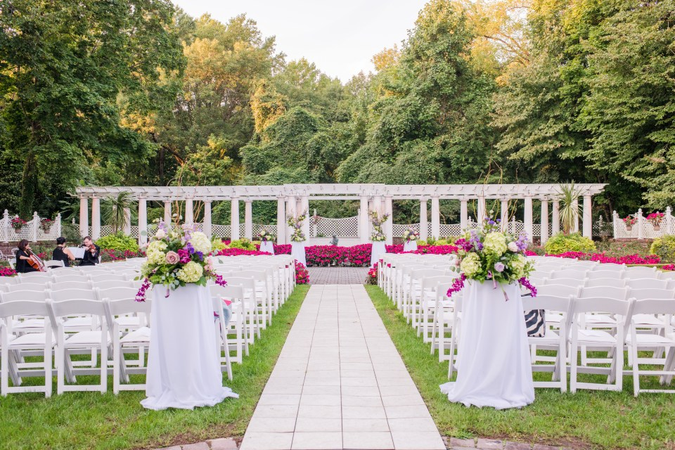 wide angle photo of the ceremony setup with white garden chairs in front of white trellis and full bloom garden at Shadowbrook at Shrewsbury