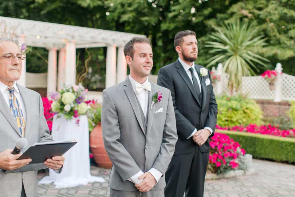 groom eagerly awaiting his bride at the end of the aisle in an outdoor ceremony at Shadowbrook at Shrewsbury