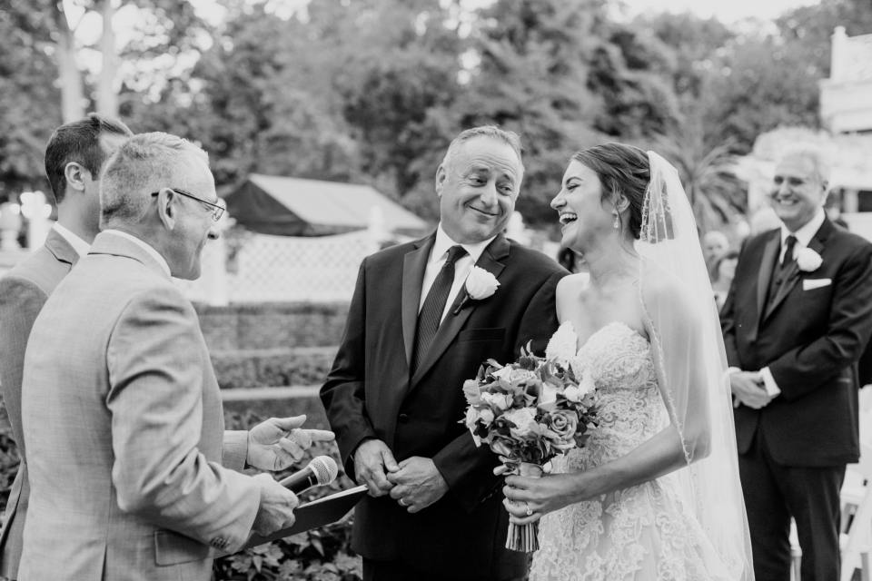 black and white candid photo of bride laughing alongside her father at the altar as he prepares to give his daughter away to her groom