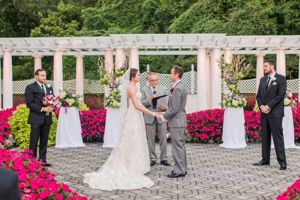 wide photo of the white trellis altar area of the outdoor wedding ceremony accented with natural pink garden flowers and the wedding florals as the bride and groom take their vows