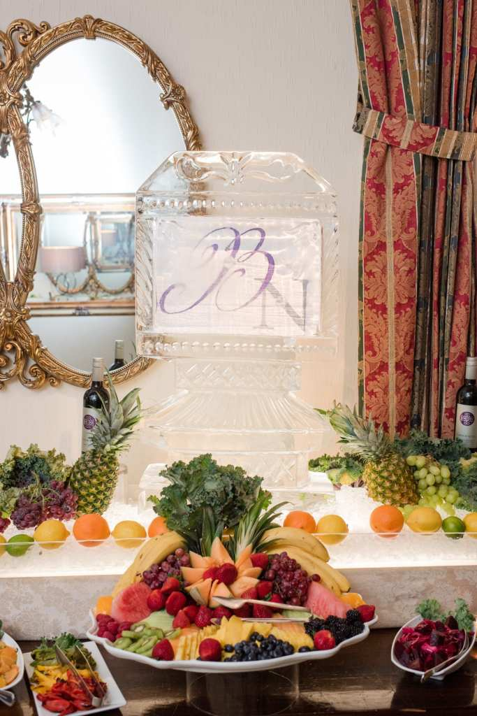 cocktail hour display of various fruits along with a personalized ice sculpture with the bride and grooms initials