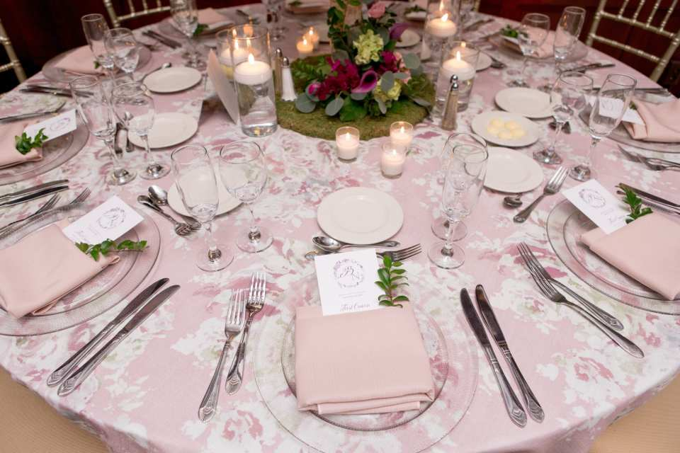 close up of reception table with light pink and lavendar floral print table linens, pink napkins, clear plate chargers, silverware, clear glassware, menu with accent greenery
