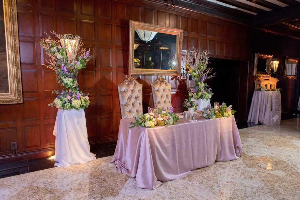 sweetheart table with shimmery lavender table linen, florals from the ceremony, tall back chairs for bride and groom, coordinating florals of hydrangeas, roses and greenery directly on table
