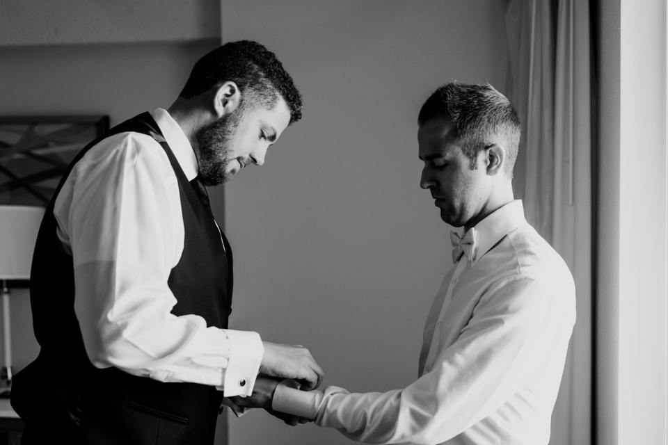black and white photo of groom being assisted with his cufflinks by a groomsman