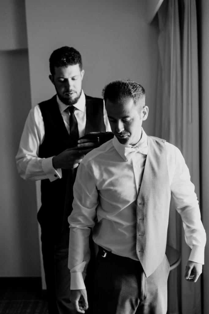 black and white photo of groom being assisted by groomsman with his vest