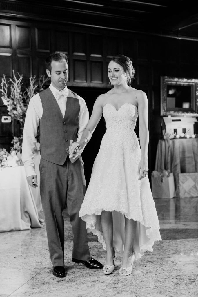 black and white photo of bride and groom about to begin their first dance. Bride in a different dress with shorter skirt in front, whereas its back is longer