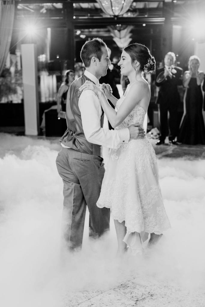 black and white photo of bride and groom surrounded by smoke on the floor during their first dance. Bride in a different dress with shorter skirt in front, whereas its back is longer
