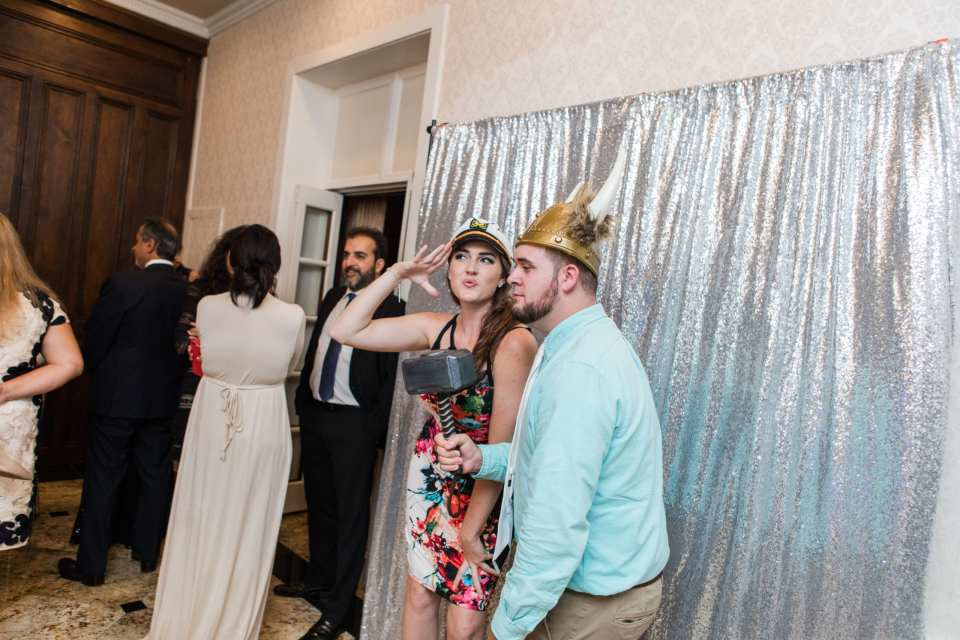 fun candid photos of wedding guests using props during photobooth snaps