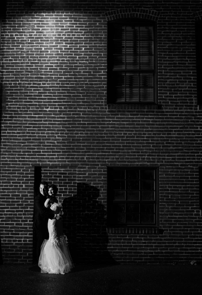 bride and groom under dim light against brick Cork Factory Hotel building