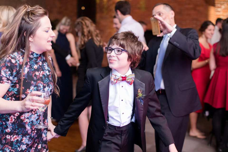 young male guest with comic book bow tie dancing during reception