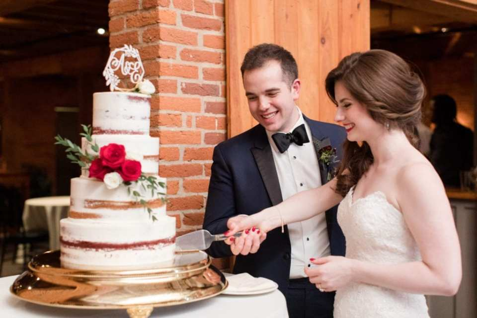 bride and groom cutting their 4 tier semi naked wedding cake with red and white rose accents