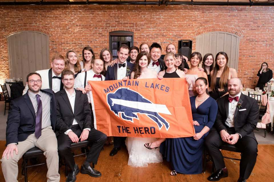 bride and groom with Mountain Lakes flag and fellow alumni