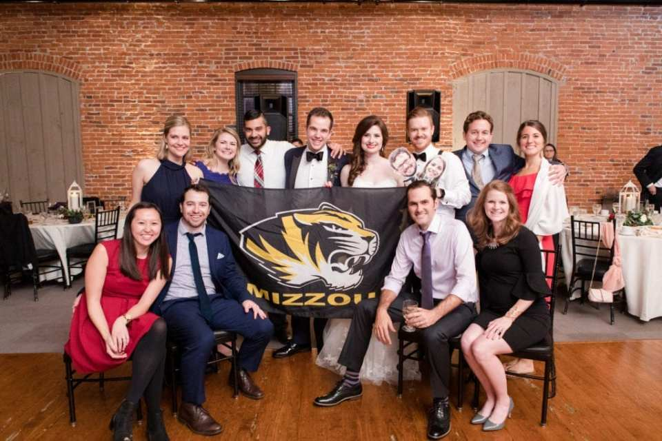 bride and groom with Mizzou flag and fellow alumni