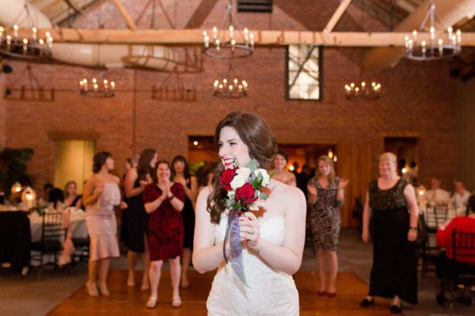 bride about to toss the red and white rose bouquet
