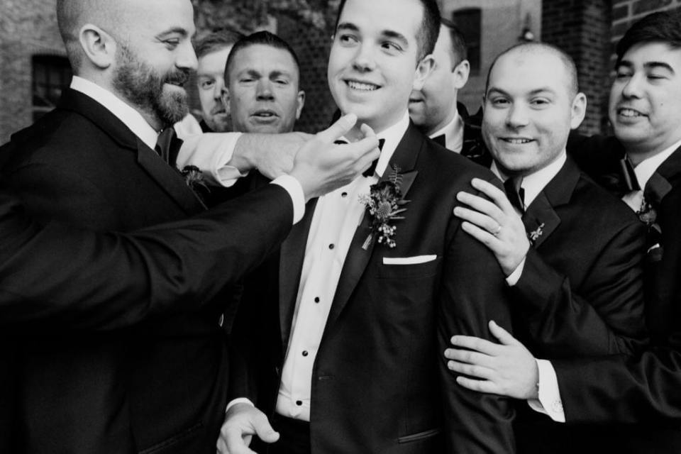black and white photo of groom being helped with his bow tie while being hugged by his groomsmen