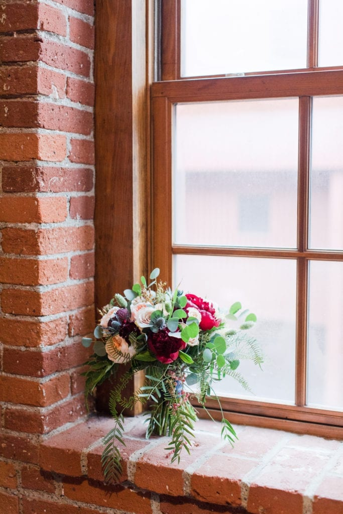 bridal party bouquet of dark red florals, cream and blush florals and greens placed in the brick window of the Cork Factory Hotel
