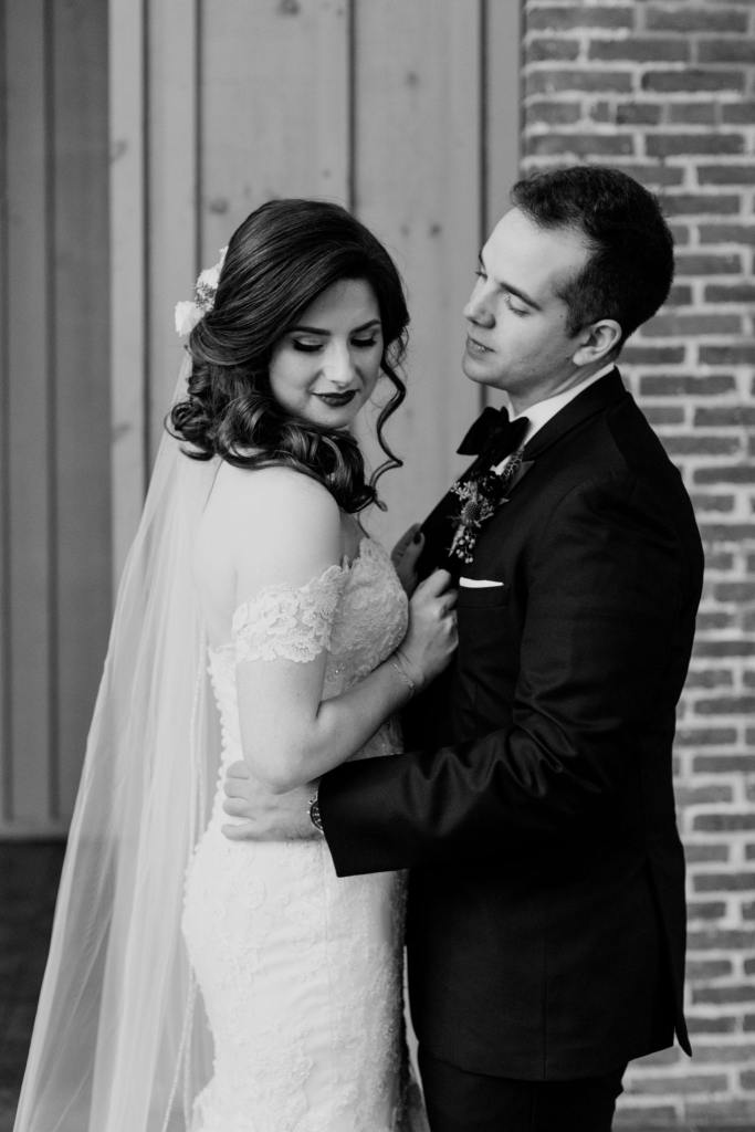 black and white photo of bride and groom looking away from camera