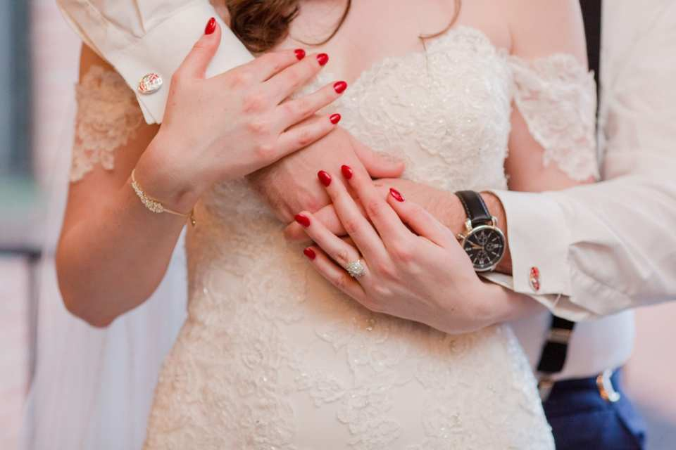 close up of hands of bride wrapped up in grooms arms in sweet smiling photo
