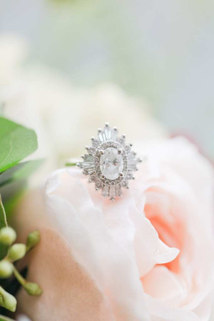 antique oval engagement ring with flower shaped halo on blush rose