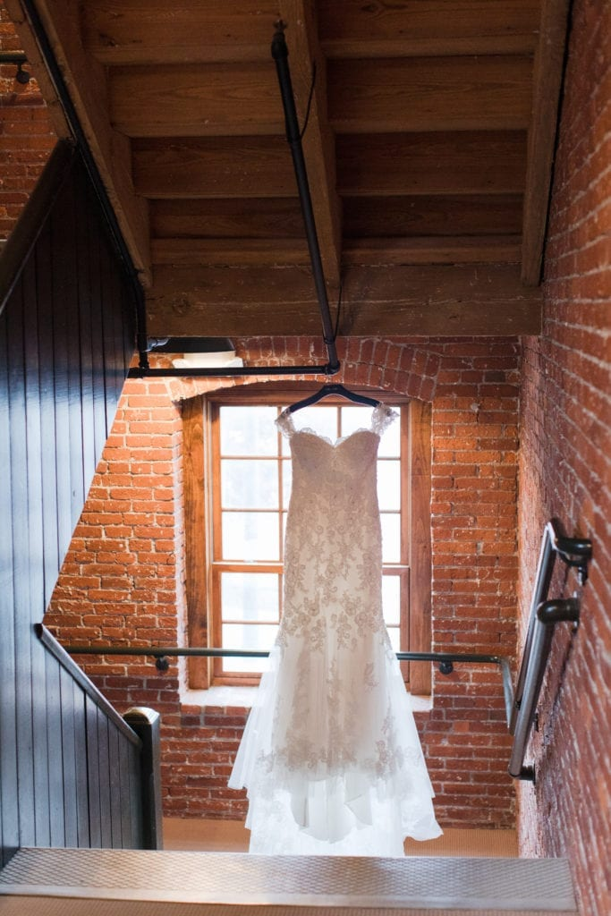 lace bridal gown hanging in brick stairwell of Cork Factory Hotel