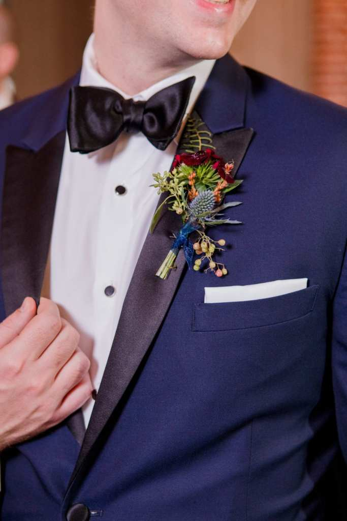 grooms boutonniere of small wild flowers and greens on his navy blue and black tuxedo lapel