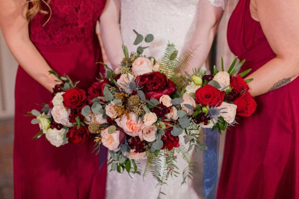 bride and bridal party holding bouquets of red roses, blush roses, greenery and dark red misc florals