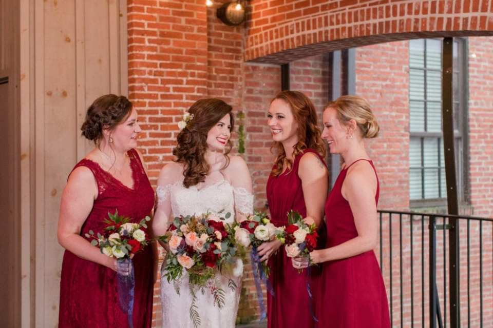 casual photo of bride and members of the bridal party looking at each other