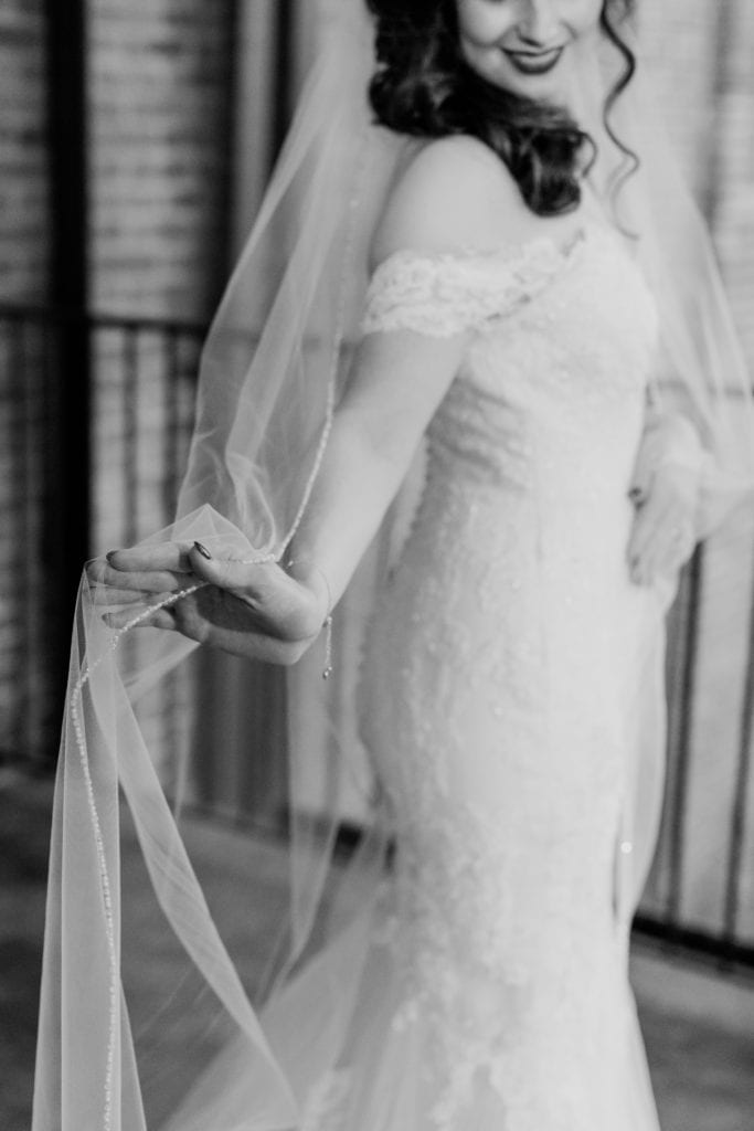 black and white photo of bride holding her veil outstretched in her right hand