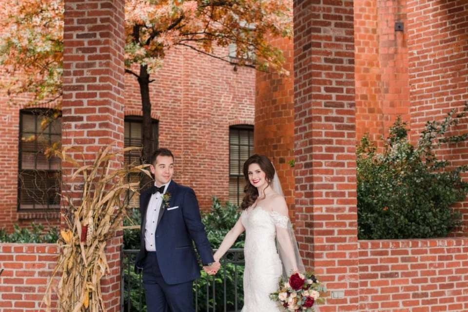 bride and groom outside of the Cork Factory Hotel in front of brick building and fall decor