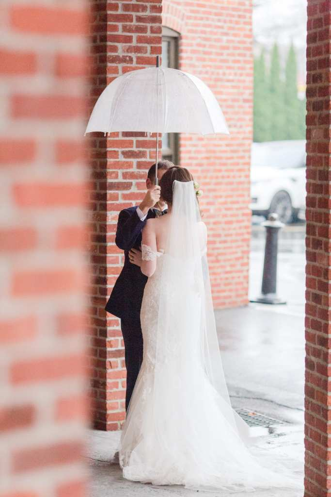 bride and groom portrait looking at each other in between brick pillars under an umbrella outside the Cork Factory Hotel