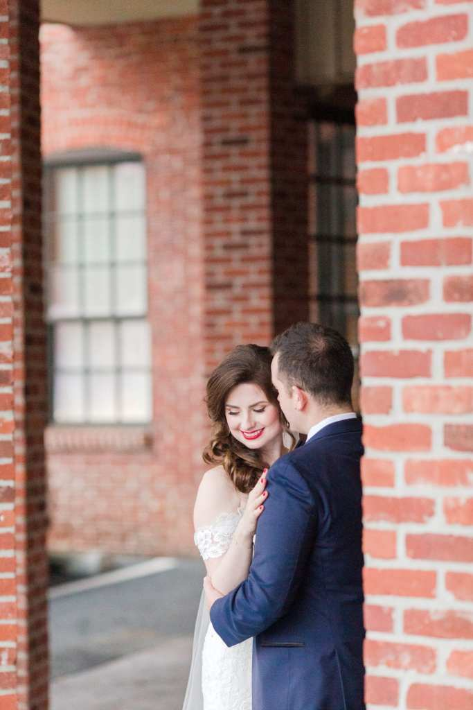 bride and groom portrait against a brick wall