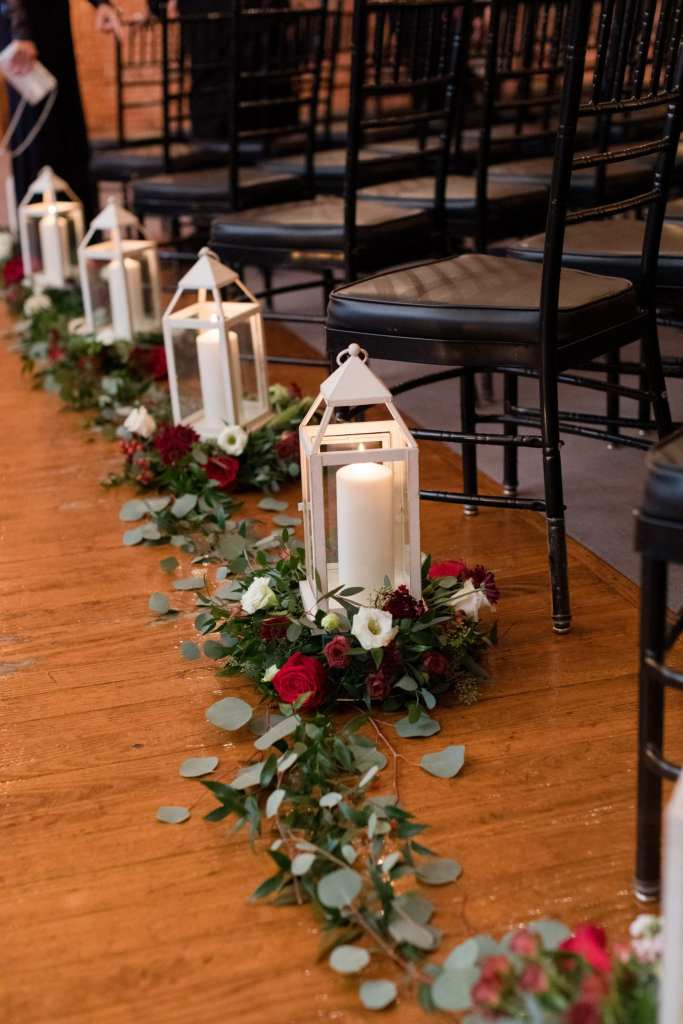 simple black chivari chairs with white linens and white candle lantern with red and white rose accents ceremony decor at the Cork Factory Hotel