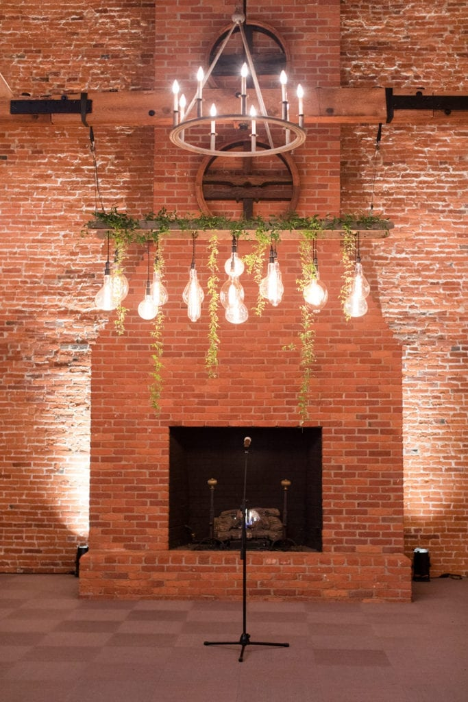 brick walled fireplace ceremony location with greens and lamps hanging down under chandelier