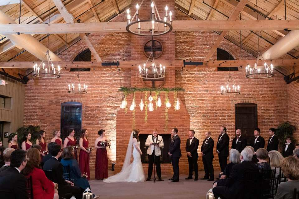 wide angle shot of bride and groom during the wedding ceremony in front of brick wall and brick fireplace with entire wedding party