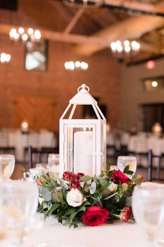 white linens and white candle lantern with red rose accent reception decor at the Cork Factory Hotel