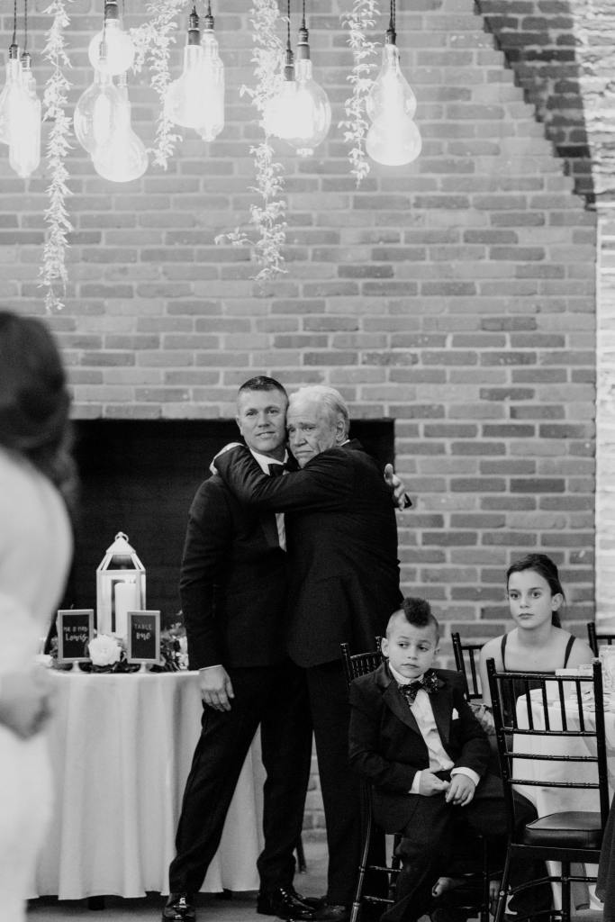 candid black and white photo of father of groom hugging best man