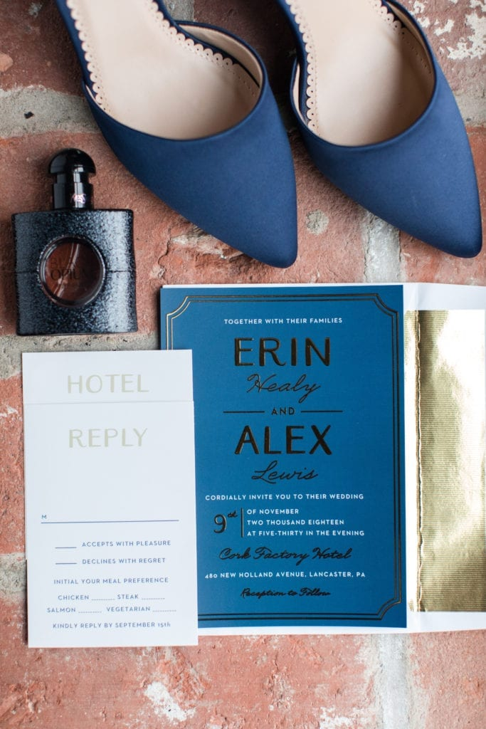 navy blue and gold invitation suite with brides navy blue shoes and parfum against a brick background