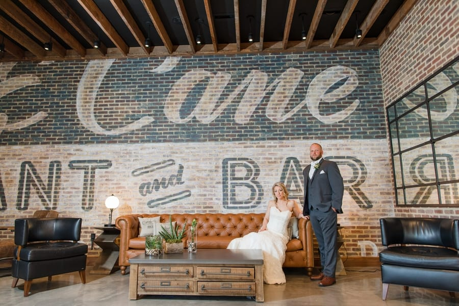 portrait of bride and groom inside lobby of Embassy Suites Berkeley Heights NJ with bride on cognac colored leather sofa and groom standing in front of brick wall