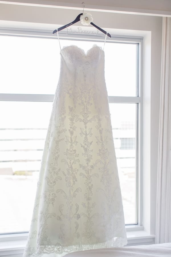 brides wedding gown hanging from a personalized hanger in front of window