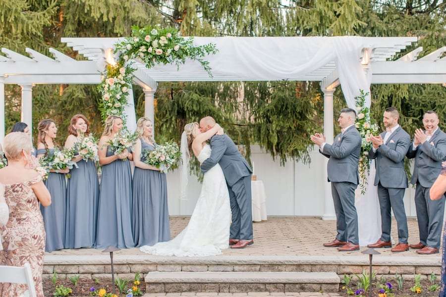the bride and groom share their first kiss as mr and mrs