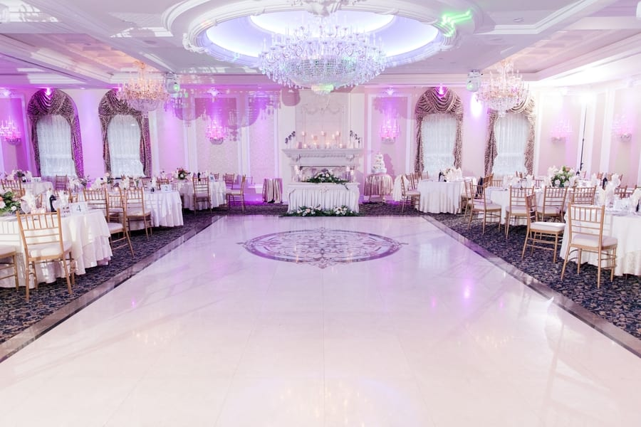 wide angle of ballroom with tables in white linens and gold chivari chairs