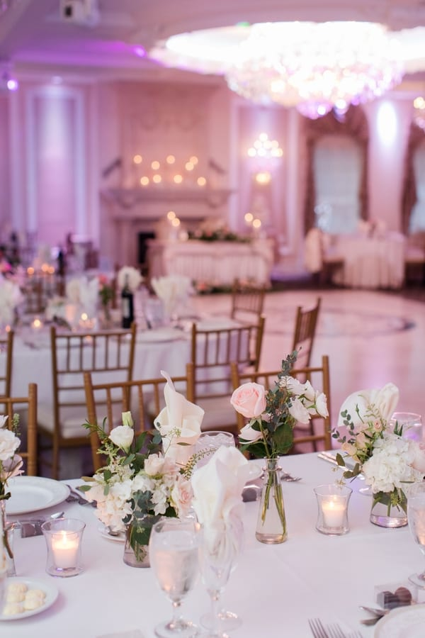 bud vases with small blush and white florals in focus with ballroom in background