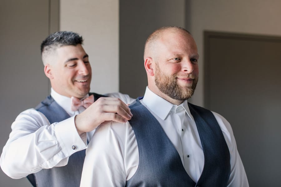 groom putting on his vest with the assistance of a groomsmen