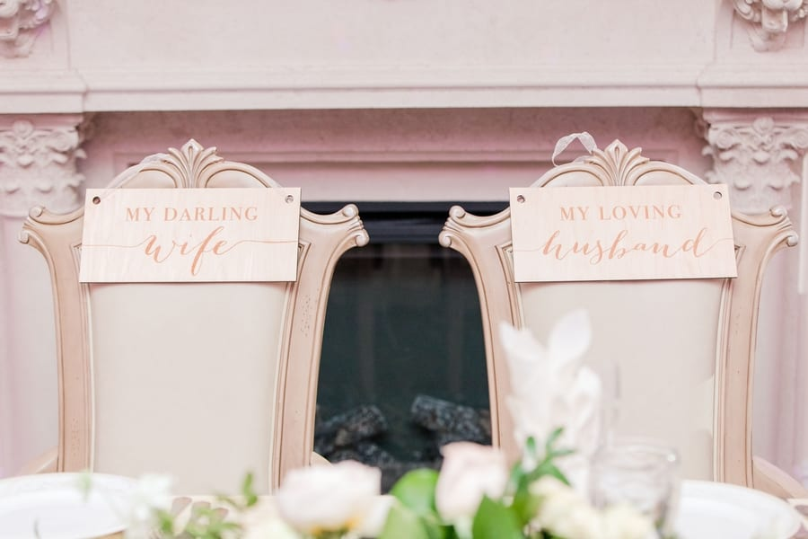 bride and groom chairs with signs