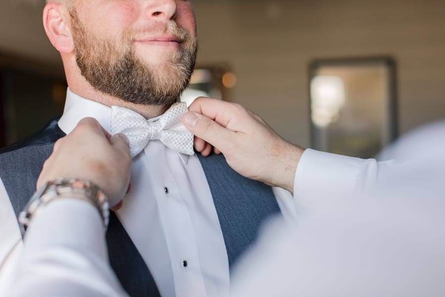 close up of grooms white patterened bow tie being adjusted by a groomsmen