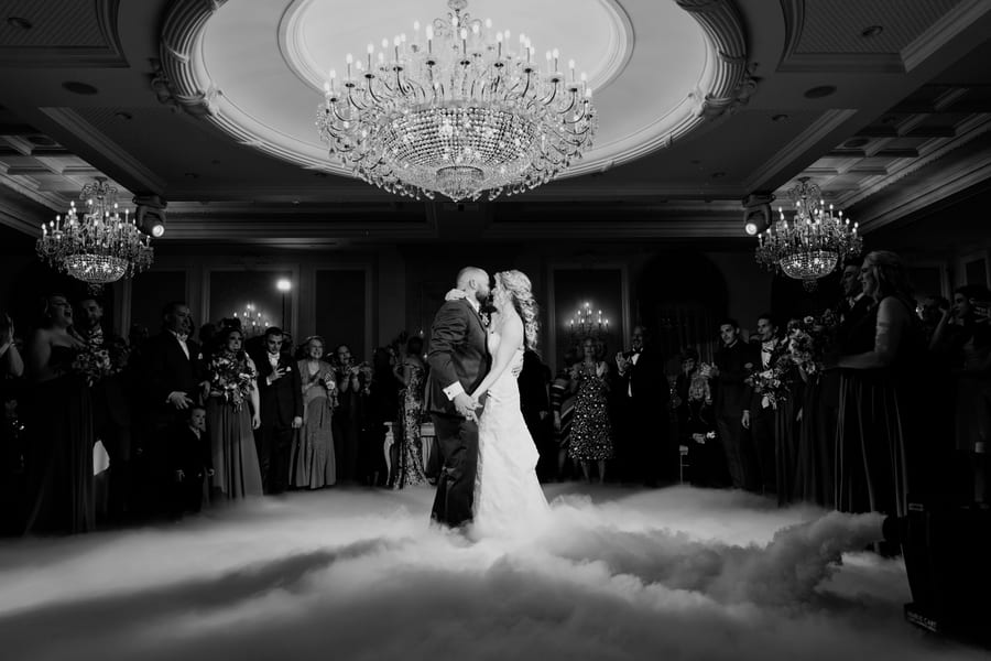 wide angle black and white photo of bride and groom dancing in fog