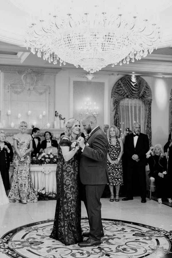 black and white full length photo of groom dancing with his mom
