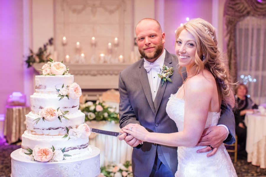bride and groom formal cake cutting photo with four tier semi nude cake with blush florals