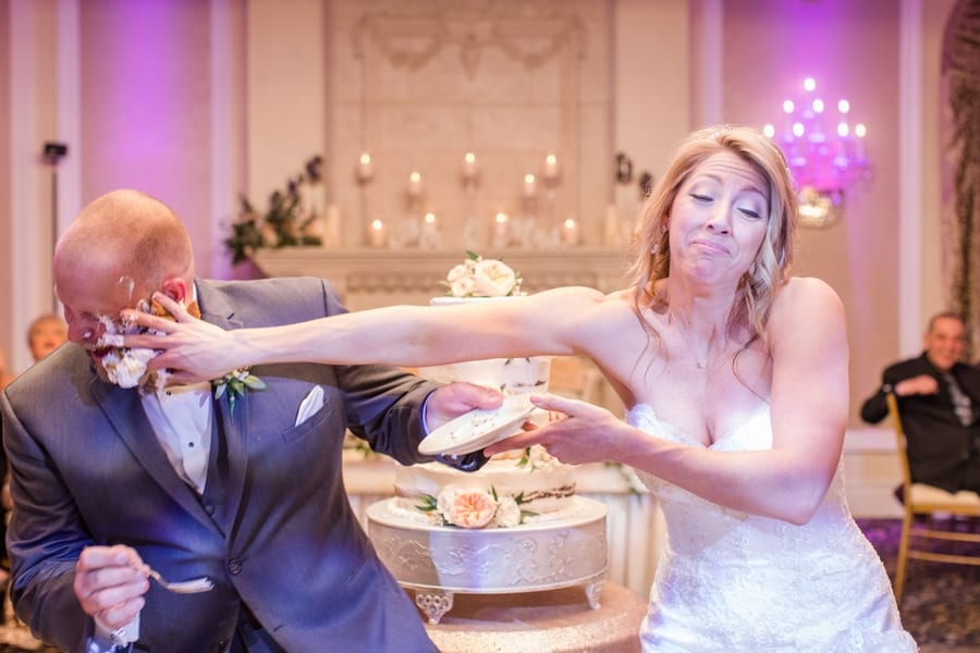 bride smashing cake on grooms face during cutting of the cake