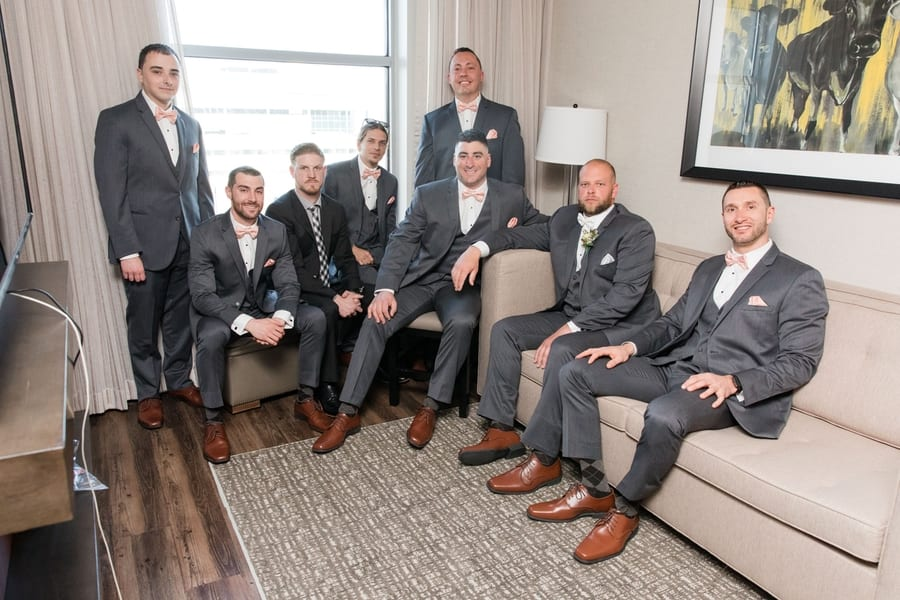 casual photo of groom and groomsmen sitting around hotel room